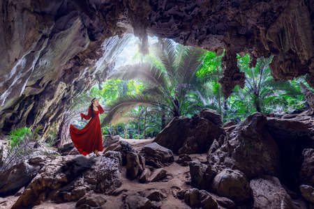 Asian female traveler in red dress exploring inside Hup Pa Tat cave in Uthai Thani Province, Thailand