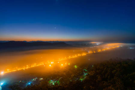 Sunrise with fog in the winter morning covers the village below in Li District, Lamphun Province, Thailand Imagens