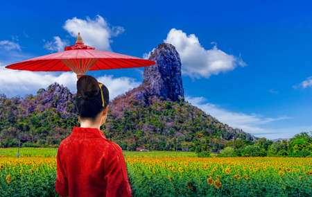 Thai woman in a Thai Lana dress holds an umbrella to watch a sunflower field with limestone hills as a background in Lopburi, Thailand.