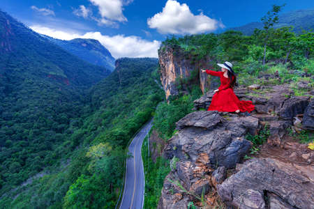 Thai woman in red dress sitting on the rock at Pha luang daeng viewpoint, Chiang mai, Thailand. Imagens