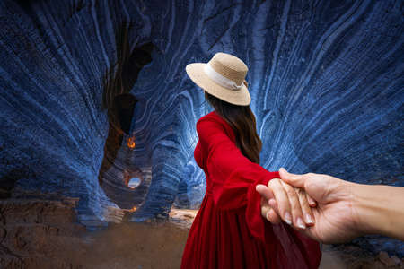 Asian woman in a red dress visits a blue cave in Tak Province, Thailand