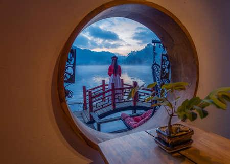 Asian female tourist stands on the wooden bridge at Ban Rak Thai village, Mae Hong Son Province, Thailand