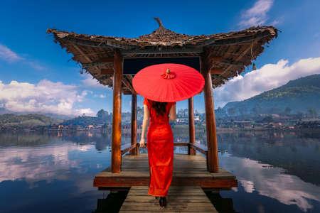 Asian female tourist stands on the water hall at Ban Rak Thai, Mae Hong Son Province, Thailand Foto de archivo