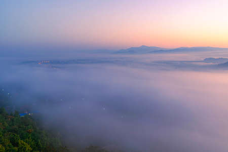 The sea of mist in the winter morning covers the village below in Li District, Lamphun Province, Thailand Foto de archivo