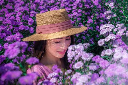 Beautiful Thai woman sitting among white flower fields in Chiang Mai, Thailand