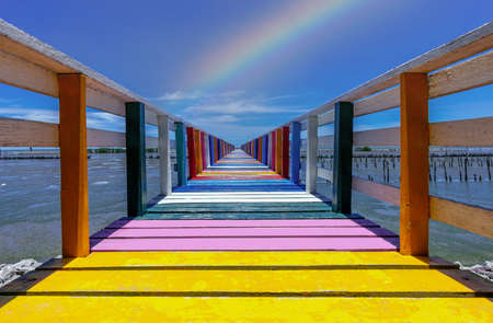 Rainbow bridge in Thailand.View of The colorful wood bridge extends into the sea under blue sky at samut sakhon province,Thailand. Foto de archivo