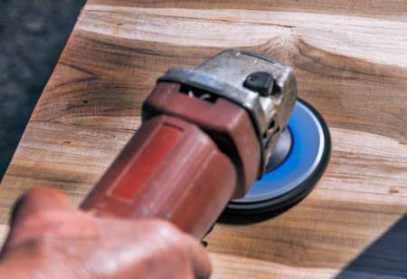 A carpenter worker is grinding a wooden surface with an electric sander Foto de archivo