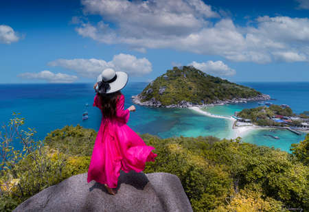 Woman in white hat and pink dress standing and enjoy the beauty on tao island clear water sky sunny nangyuan view point paradise