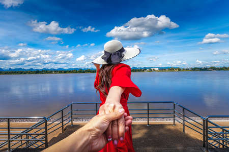 Tourists hold hands while looking at the Mekong River view in Nakhon Phanom Province, Thailand Foto de archivo