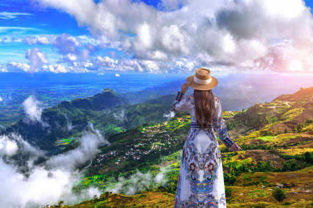 Asian woman looking beautiful landscape of Phu tub berk. agriculture village on the mountain with layer mountain and cloudy Foto de archivo