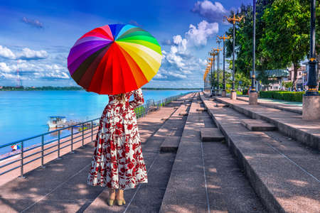 Thai woman holding a rainbow umbrella stands on the banks of the Mekong River in Nakhon Phanom Province, Thailand
