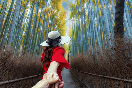 A woman tourist is hand to hand sightseeing and traveling at Arashiyama Bamboo Forest in Kyoto, Japan. Foto de archivo