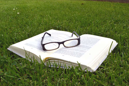 book and glasses on the grass background