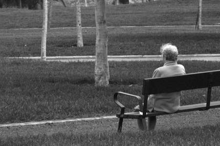 inhabitants: old woman sitting on a park bench black and white