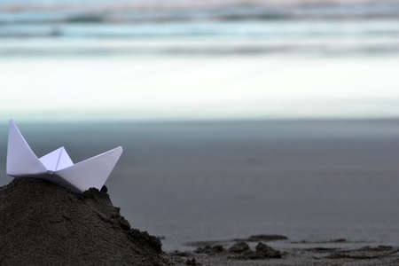 Paper boat on beach photo