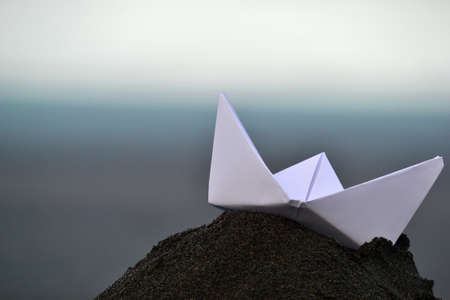 Paper boat on sand photo