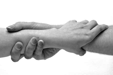 a helping hand: Black and white hands clasped Stock Photo