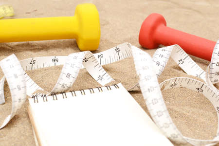 sports shell: Notebook and dumbbells on sand Stock Photo