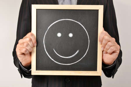 Businessman with smiling face in blackboard photo