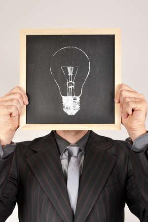 Businessman and bulb in blackboard photo