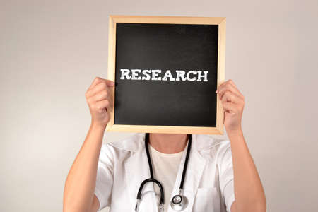 sic: Doctor with a blackboard in front of face Stock Photo