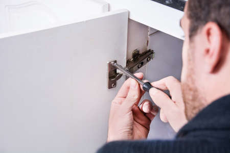 yard stick: Man fixing a cabinet with a screwdriver Stock Photo