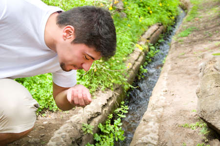 grasp: Man drinking water from the stream Stock Photo