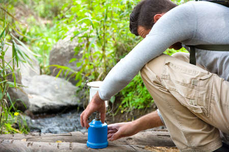 man with camping gas in nature Stock Photo
