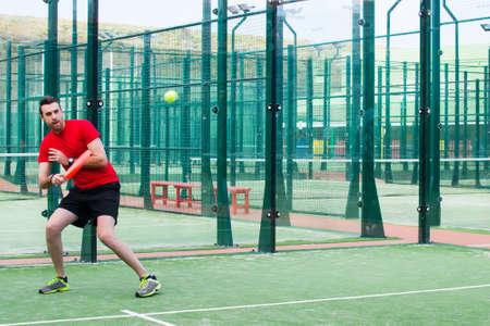 man playing paddle tennis