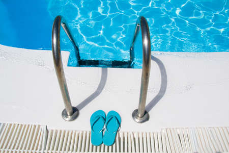 summer shoes: swimming pool and summer shoes Stock Photo