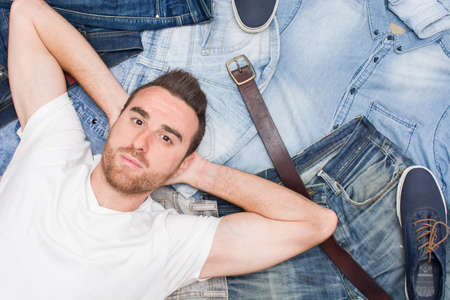 jeans: man lying on many jean clothes Stock Photo