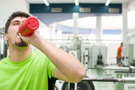 man drinking water: man drinking water in gym Stock Photo