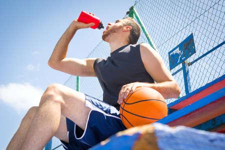 bleachers: Young man drinking water in bleachers of basketball field
