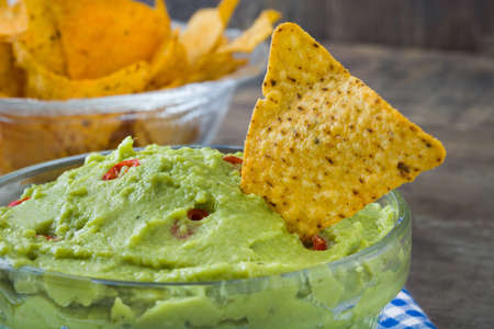 nachos: Nachos and guacamole on wood Stock Photo