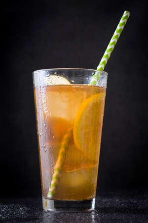 Ice tea with lemon. Black stone background