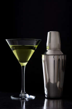 martini shaker: Green apple and cocktail shaker on black stone background