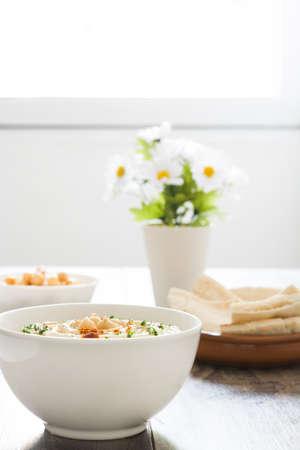 hummus: Hummus in bowl on rustic wood