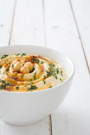 Hummus in weißer Schale auf weißem Holz Standard-Bild - 56967584