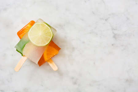 popsicle: Orange and lime popsicle popsicle on marble table