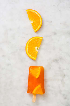 popsicle: Homemade orange popsicle on marble Stock Photo