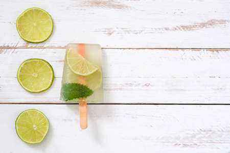 popsicle: Lime popsicle on white wooden table