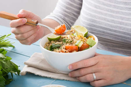 Woman eating quinoa and vegetables