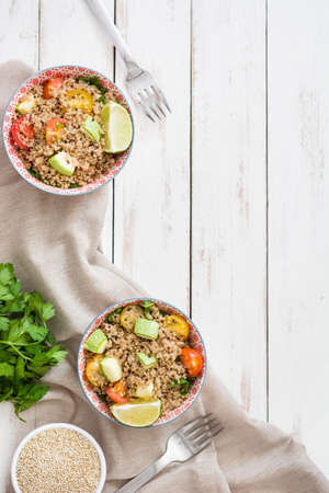 Quinoa with tomatoes, zucchini and lime on white wooden table Stok Fotoğraf