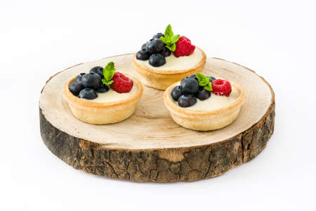 summer pudding: Delicious tartlets with raspberries and blueberries on tree trunk isolated Stock Photo