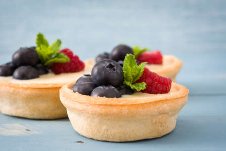 summer pudding: Delicious tartlets with raspberries and blueberries isolated on blue background