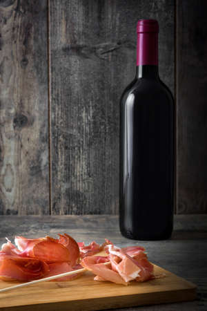 serrano: Thin slices of Spanish serrano ham and wine bottle Stock Photo