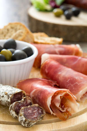 serrano: Spanish serrano ham, olives and sausage on a rustic wooden table