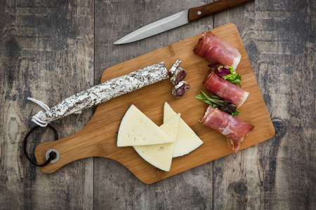 serrano: Spanish serrano ham, cheese and sausage on a rustic wooden background