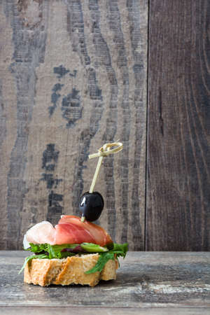 serrano: Spanish serrano ham skewer with olives and lettuce on a rustic wooden background