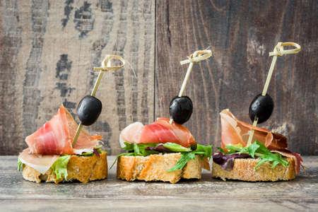 Espagnol brochettes de jambon serrano avec des olives et la laitue sur un fond en bois rustique